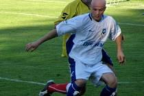 Záložník Kyjova Radek Bužek (v bílém) si kryje míč před dotírajícím hráčem Břeclavi.