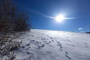 Sluncem zalitá krajina je ještě plná sněhu. I přesto se dá krásně projít.