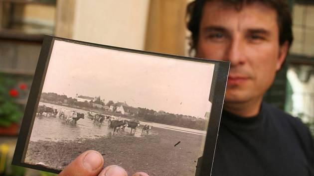 Kastelán milotického zámku Evžen Boček drží pohlednici, na které je fotka pořízená hrabětem Seilernem.
