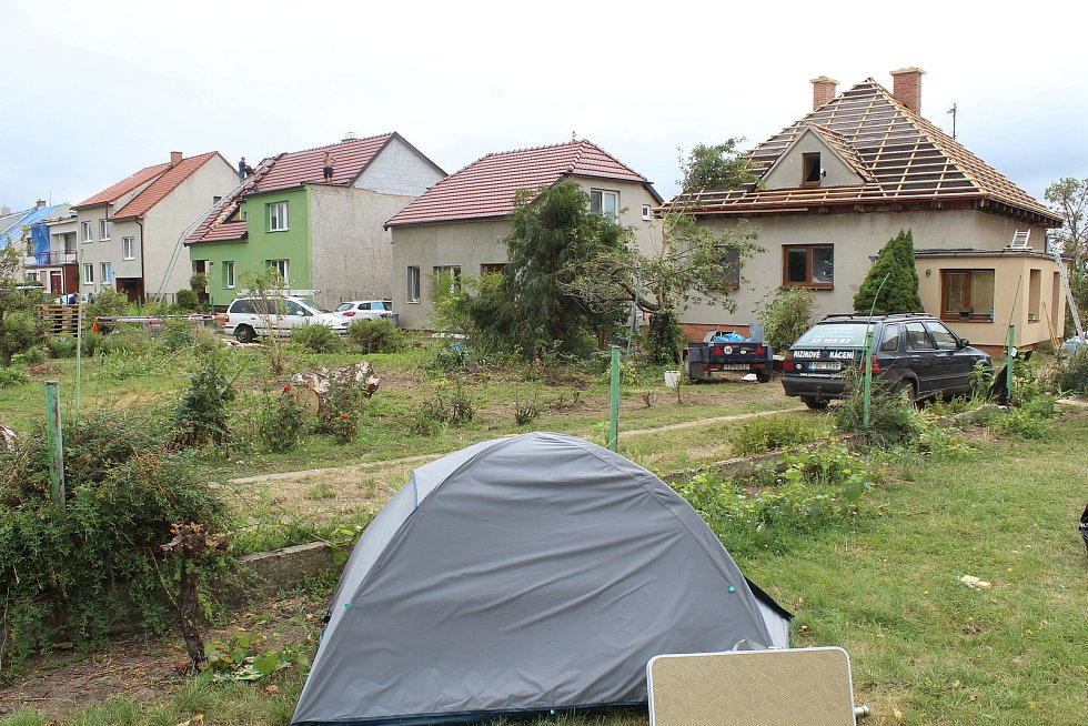 Poškozená část Mikulčic směrem na Moravskou Novou Ves, dva týdny po tornádu. Někteří řemeslníci tady také stanují.