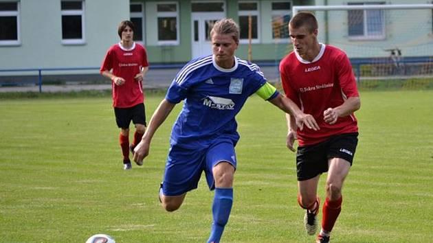 Rohatečtí fotbalisté zvítězili na hřišti ve Strážnici 2:1. Hostujícího kapitána Jakuba Tomšeje (v modrém dresu) střeží domácí útočník Karel Paška.