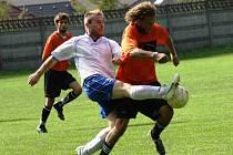 Záložník Žarošic Lukáš Přikryl (v oranžovém) se snaží přejít přes bránícho hráče Starého Poddvorova. Domácí tým nakonec vyhrál v 7. kole první B třídy 2:0.