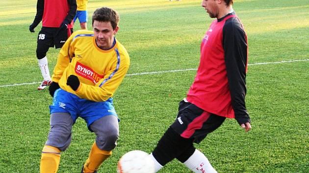 Obránce Ratíškovic Milan Koplík (ve žlutém) posílá míč přes záložníka Vracova Eliáše (v červeném).
