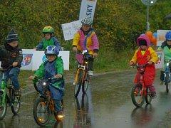 Děti jedou po nové cyklostezce se znaky obcí na kolech.