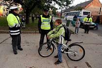 Policisté kontrolují mladé cyklisty před školou.