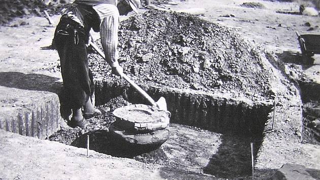 ARCHEOLOGICKÉ VYKOPÁVKY NA DÁLNICI. Dělník odkrývající vypalovací pec z pozdní doby kamenné.