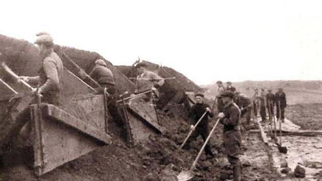 Dělníci skládají materiál z vozíků úzkorozchodné železnice na stavbě autostrády.j