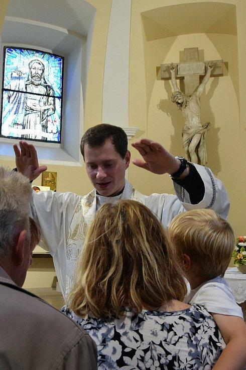 Po mši udílel novokněz věřícím požehnání v kostele.