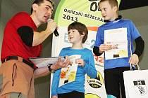 Ředitel Okresní běžecké ligy Jiří Vrtílka předává ceny v dětskcýh kategoriích při závěrečném vyhlášení výsledků.