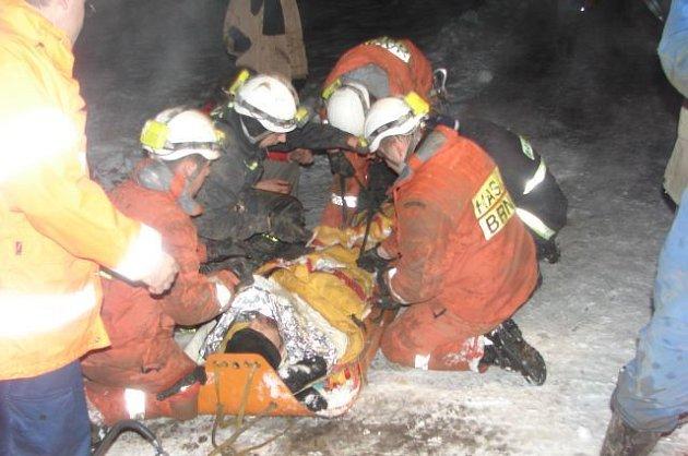 Záchranáři připravují muže na přesun sanitkou do nemocnice.