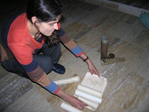 Evangleická farářka ukazuje nalezené dokumenty.