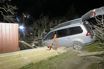 Zaparkované auto, do kterého opilý řidič boural, skončilo v plotu vedlejšího domu.