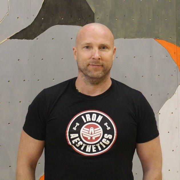 Michal Vorlický před lezeckou stěnou.