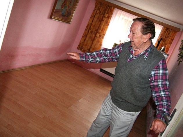 Třiaosmdesátiletý Bohuslav Zachoval z Černovic ukazuje ve svém domě, kam až sahala voda při pondělní bleskové povodni.