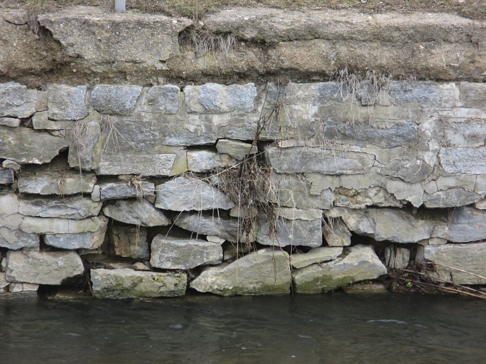 Zkroucené a místy vyvrácené zábradlí. Rozdrolená opěrná zeď, ve které jsou velké díry. Asi metr a půl pod silnicí pak teče potok Úmoří. Tak vypadá několik desítek metrů dlouhý úsek při výjezdu z Drnovic ve směru na Skalici nad Svitavou.