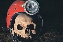 Zátiší se speleologickou helmou a objevenou lebkou.