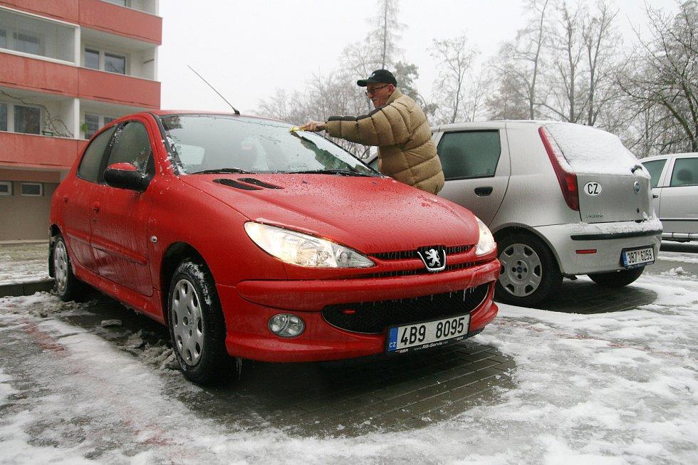 Ledovka komplikovala provoz v regionu od nedělního večera. Na snímku řidič čistí auto od ledu v adamovské ulici Družstevní.