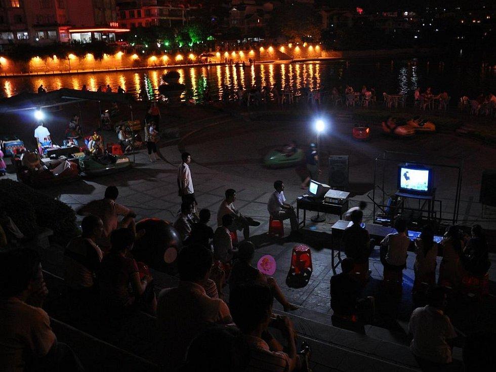u řeky Li se po večerech posedává, hrají společenské hry, jezdí na šlapacích autíčkách a pořádají soutěže v karaoke