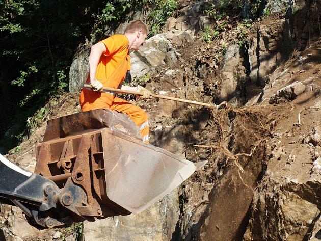 Silničáři upravují skálu u silnice, aby z ní nepadaly kameny.