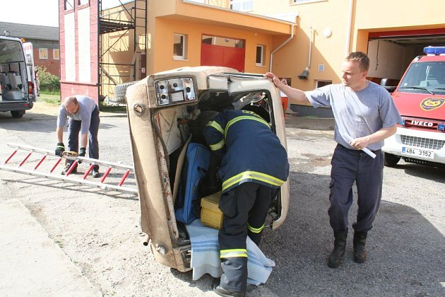 Hasiči zajišťují havarované vozidlo a poskytují první pomoc.