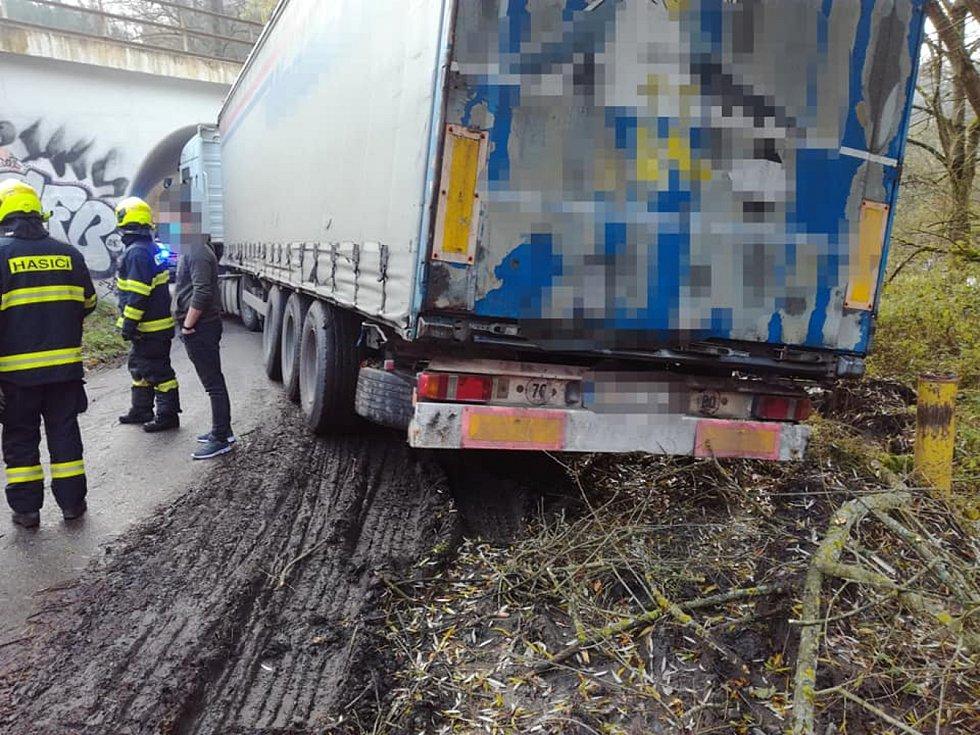 Cizinec zablokoval lesní cestu. S kamionem uvízl pod tratí.