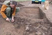 Archeolog Petr Kos z Ústavu archeologické památkové péče v Brně odkrývá část pece v slovanském hutnickém objektu.