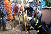 Hasiči zachraňují muže ze studny.