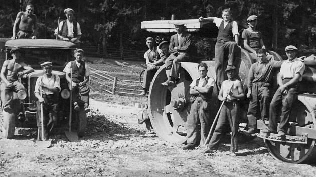 Stavba dálnice Pod Horkou, léto 1940. Na snímkuta dělníků u náklaďáku a silničního válce.  par