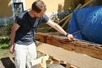 Muži zavěšení vysoko nad střechami okolních domů shazují ze špičky kostela ve Strachoticích jednu prohnilou dřevěnou lať za druhou. A nahoru vytahují ručně opracované trámy, které nahradí desetiletími a dřevomorkou zničené původní.