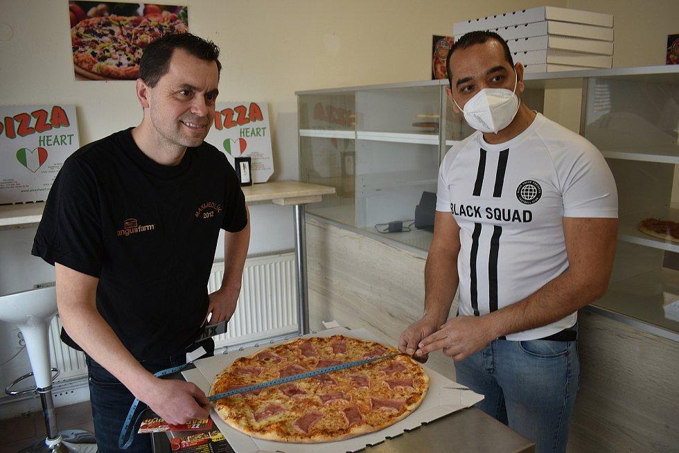 Maxijedlík Jaroslav Němec slupl půlmetrovou pizzu. Za devět minut. Na snímku s ním je majitel boskovické pizzerie Heart Mohamed Ali. Na rekordní pokus mu v sobotu upekl sýrovou pizzu s feferonkami.