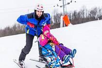 Instruktor Tomáš Procházka na svahu v Němčičkách s monoski a malou Sabinkou Grofovou, která má mozkovou obrnu.