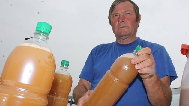 Miloslav Machuča starší nabízí plastové láhve naplněné burčákem na břehu rybníku Apollo mezi Břeclaví a Lednicí.