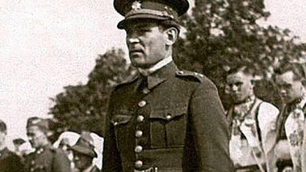 Učitel Josef Kocůrek salutuje v uniformě při pohřbu ruských vojáků po osvobození v roce 1945.