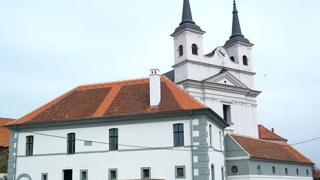 Obnovená stará drnholecká radnice (v popředí) a za ní památkově chráněný kostel z osmnáctého století.