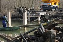 U Janohradu roste nový most přes řeku. Dělníci v úterý pokládali přes vodu mostovku, den před tím strhli zbytky staré lávky, kterou před lety postavili filmaři.