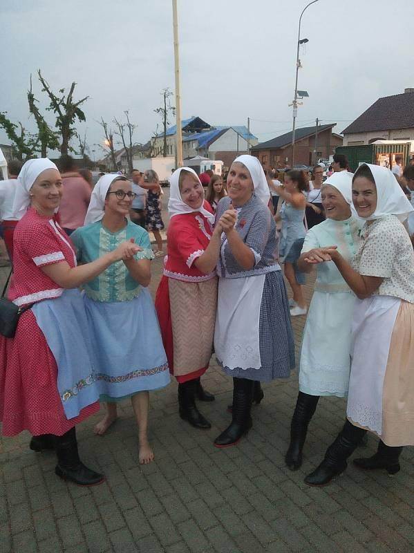 Členky valtického ženského pěveckého sboru Výběr z bobulí pomáhají kolegyním z Ženského sboru z Moravské Nové Vsi, které tornádo připravilo o kroje.