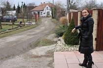 Břeclavská ulice U Lesa poblíž řeky Dyje. I když v těchto dnes prakticky neprší, cesta je stále vlhká se stopy bláta. Každý další déšť způsobuje Petře Černé a dalším majitelům okolních domů obtíže.