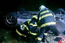Po střetu dvou osobních aut zůstalo jedno z nich mimo silnici na střeše. V něm cestovaly dvě osoby.