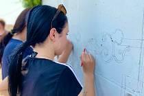 Hustopečští pomalují volnou zeď ve Vinařské ulici.