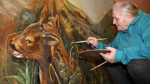 Lidová umělkyně Rozína Lhotská – Bollová opravuje obří nástěnnou malbu.