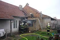 Kvůli rozšíření požáru museli hasiči udělat díry i do střechy domu ve Starovičkách.