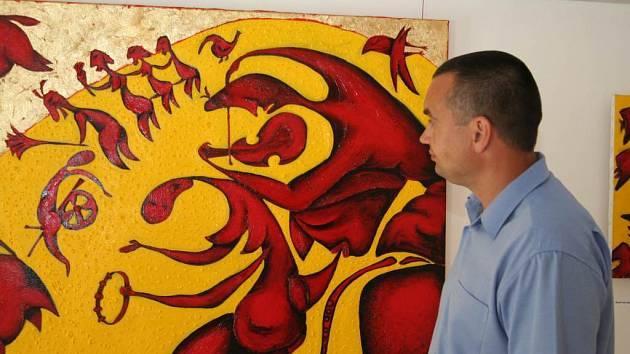 Vedoucí kulturního odboru Zbyněk Tureček si prohlíží jeden z vystavovaných obrazů.