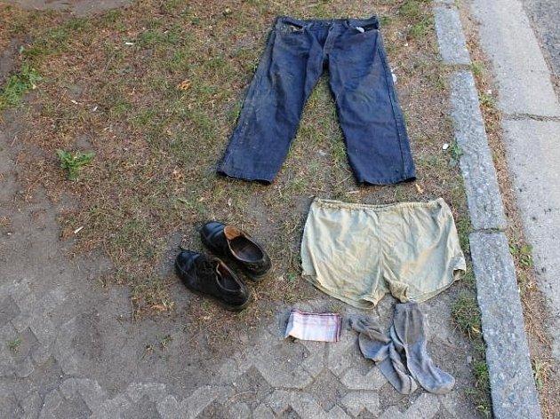 Muž měl na sobě oblečené modré rifle, zelené spodní prádlo, šedé ponožky a na nohou černé polobotky.
