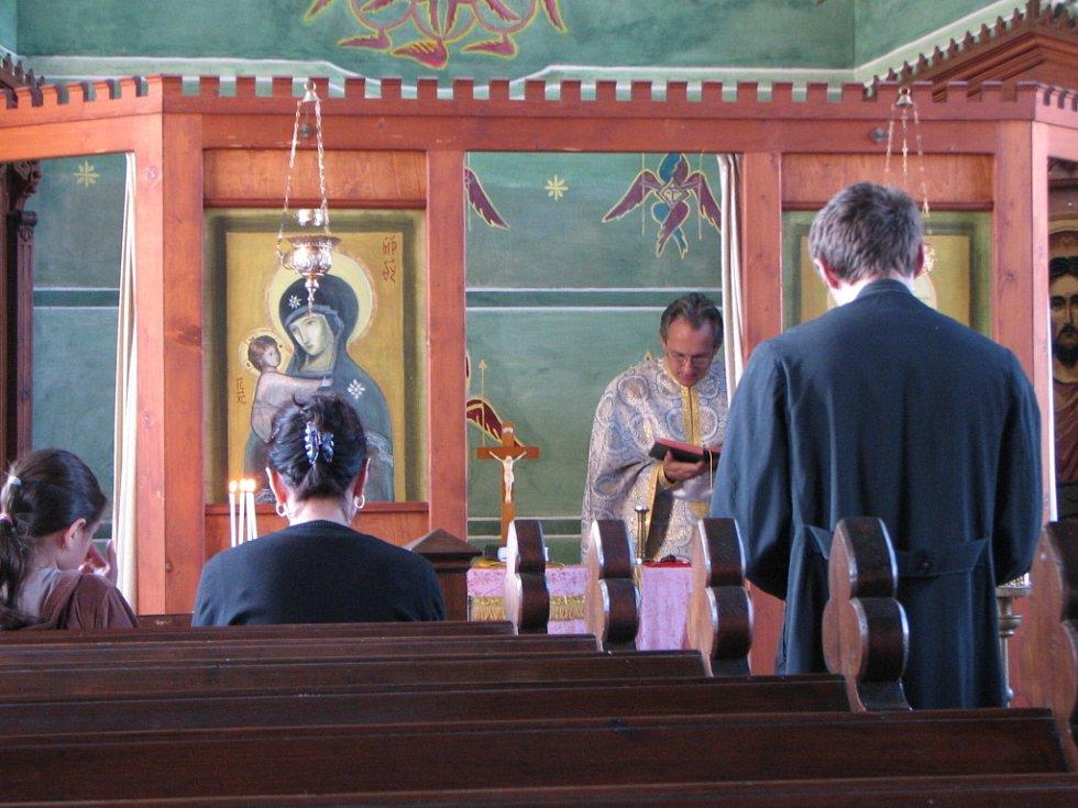 Otec Flaviu Badelita slouží před věřícími, z nichž většina jsou cizinci, kteří přijeli za prací, pravoslavnou bohoslužbu.