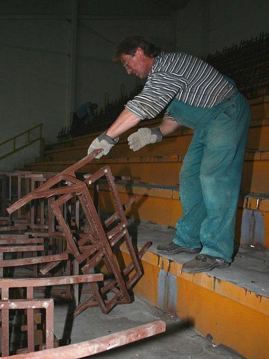 Dělníci demontují staré sedačky na tribunách břeclavského zimního stadionu.