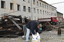 Kopa dřeva a dělníci na střeše. Demolice šedé budovy u břeclavského nádraží, bývalého útočiště bezdomovců, je v plném proudu. Někteří kolemjdoucí nepohrdli ani mokrým dřevem, které se při rozebírání střechy zatoulalo pod zábranu.