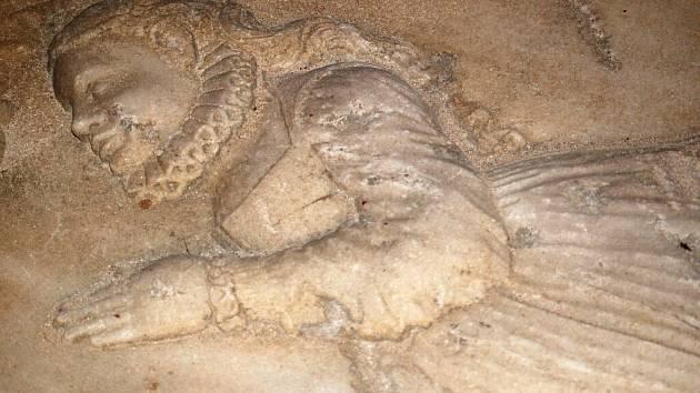 Podzemní krypta se starými náhrobními kameny.
