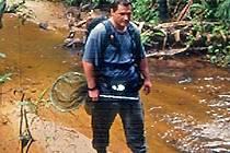 Člen výpravy prochází korytem řeky.