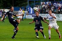 Břeclavský Patrik Levčík (v bílém) bojuje s přesilou fotbalistů Slovácka.