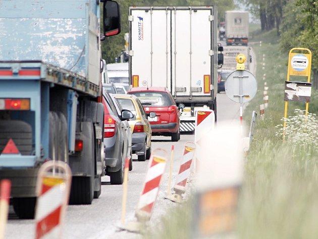 Řidiči projíždějí opatrně křižovatkou u Starovic po státní silnici mezi Velkými Němčicemi a Hustopečemi. Opravy silnice a omezení provozu semafory a značkami tam zapříčinily větší či menší kolony. I mimo dopravní špičku lidé s auty stojí na místě několik